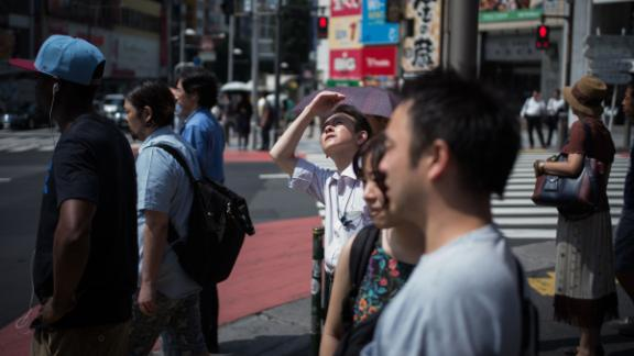 A man in Tokyo shields his eyes from the sun on Tuesday, July 24. Dozens of people have died across Japan as the country continues to swelter under scorching summer temperatures.