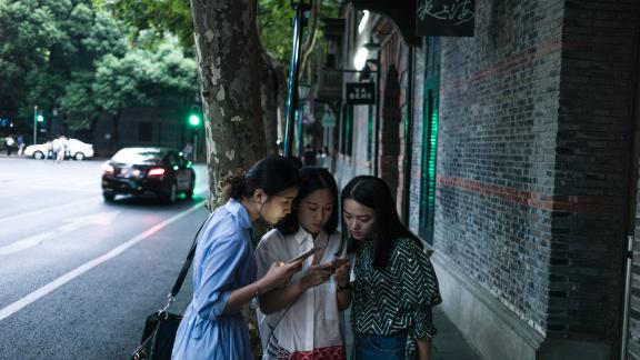 Women look at their smartphones in Xintiandi district, a shopping area, in Shanghai on September 8, 2016. / AFP / FRED DUFOUR        (Photo credit should read FRED DUFOUR/AFP/Getty Images)
