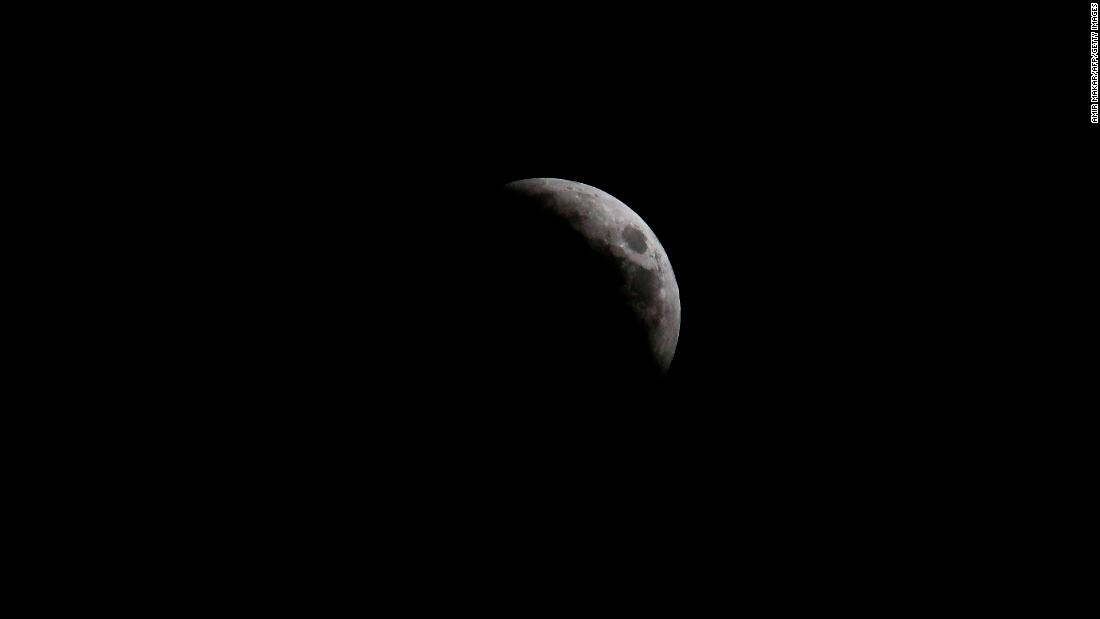 The moon is seen from Nicosia, Cyprus, as the eclipse began to become visible.