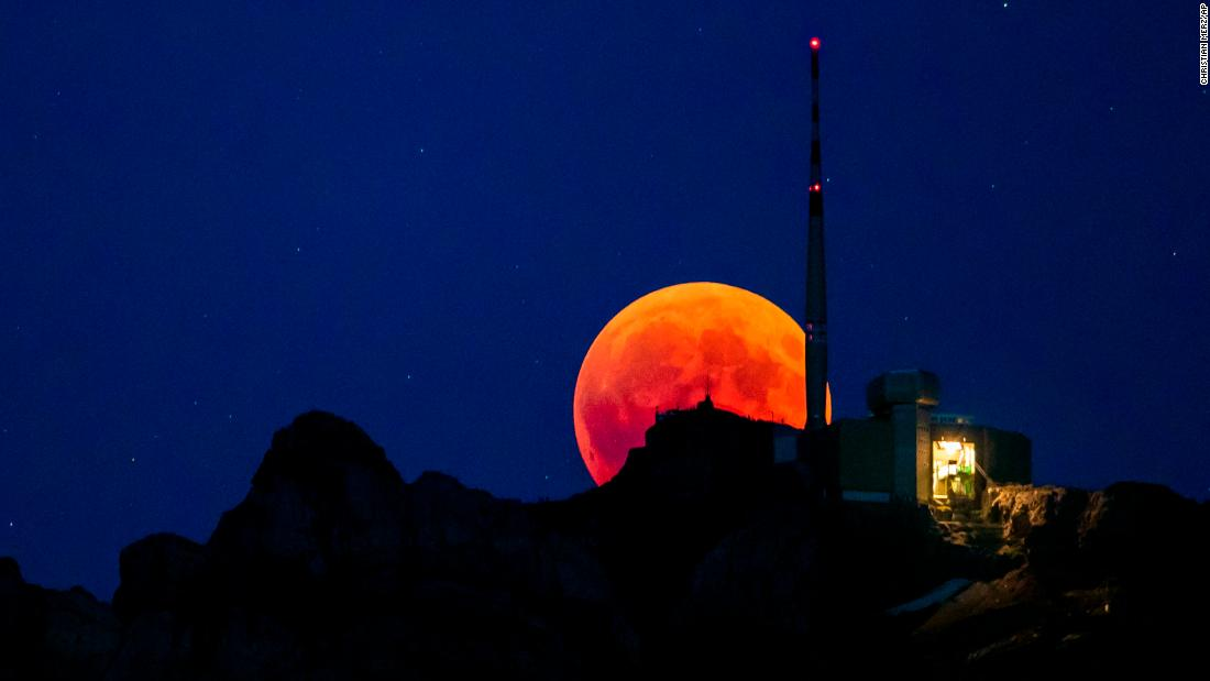The blood moon is seen behind a mountain in Lucerne, Switzerland.