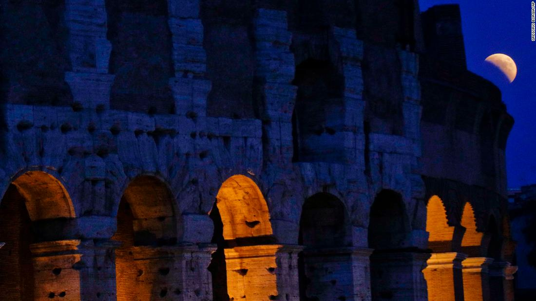 The moon peeks out next to the Colosseum in Rome.