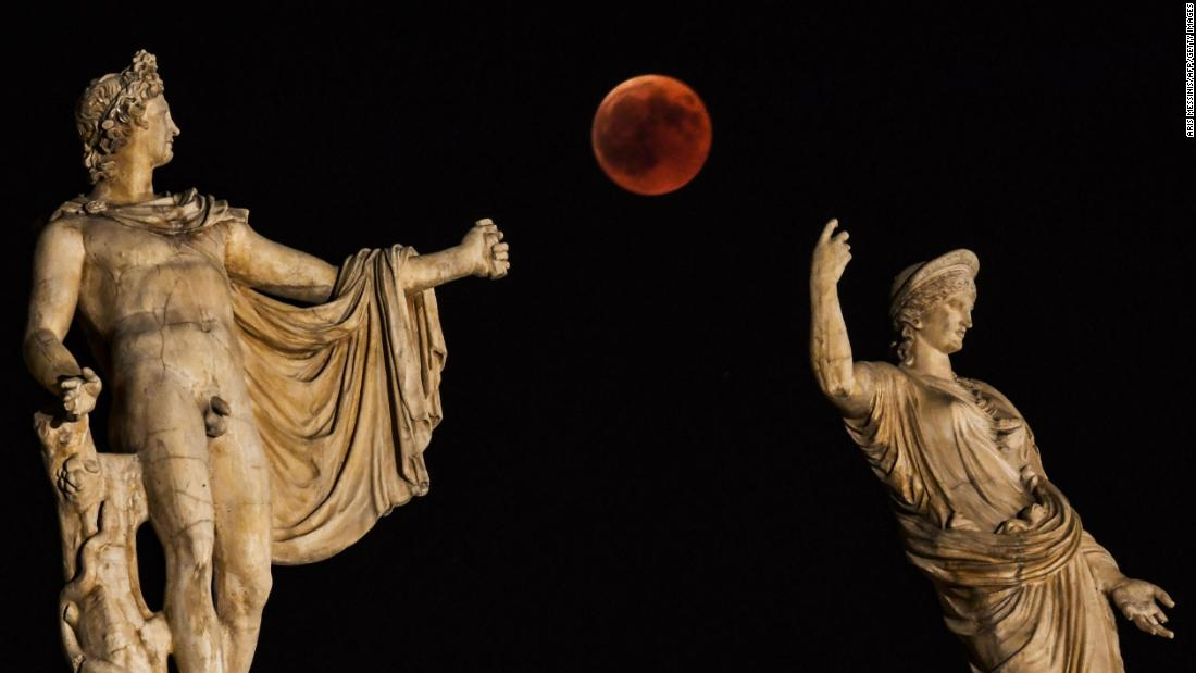 The blood moon is framed by the statues of Hera and Apollo in Athens, Greece.