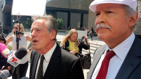 Attorneys Peter Schey, left, and Carlos Holguin field questions from reporters outside the federal courthouse in Los Angeles on Friday.
