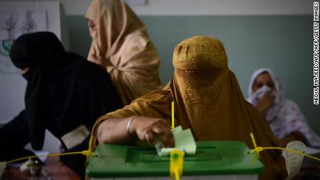 A burqa-clad woman casts her vote during Pakistan's general election at a polling station in Peshawar.