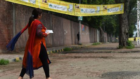 A Pakistani woman walks to cast her vote.