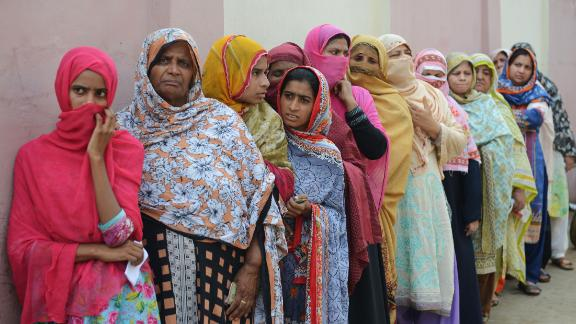 TOPSHOT - Pakistani women stand in a queue as they wait to cast their vote outside a polling station during general election in Lahore on July 25, 2018. - Pakistanis vote on July 25 in elections that could propel former World Cup cricketer Imran Khan to power, as security fears intensified with a voting-day blast that killed at least 30 after a campaign marred by claims of military interference. (Photo by ARIF ALI / AFP)        (Photo credit should read ARIF ALI/AFP/Getty Images)