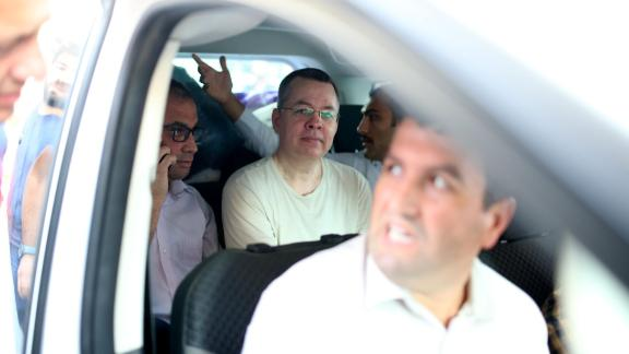 Andrew Brunson, center, is seen inside a car escorted by Turkish plain-clothes police officers as he arrives at his house in Izmir on July 25.