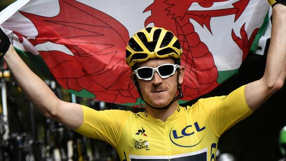 Geraint Thomas proudly holds the Welsh flag as he rides to victory on the final stage of the 105th Tour de France.