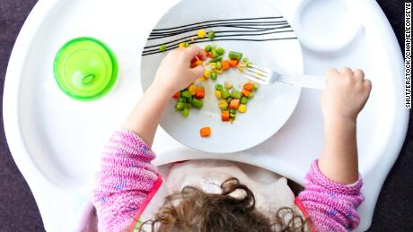 Above view of a little toddler child eats vegetables. Childhood and children health care concept.
