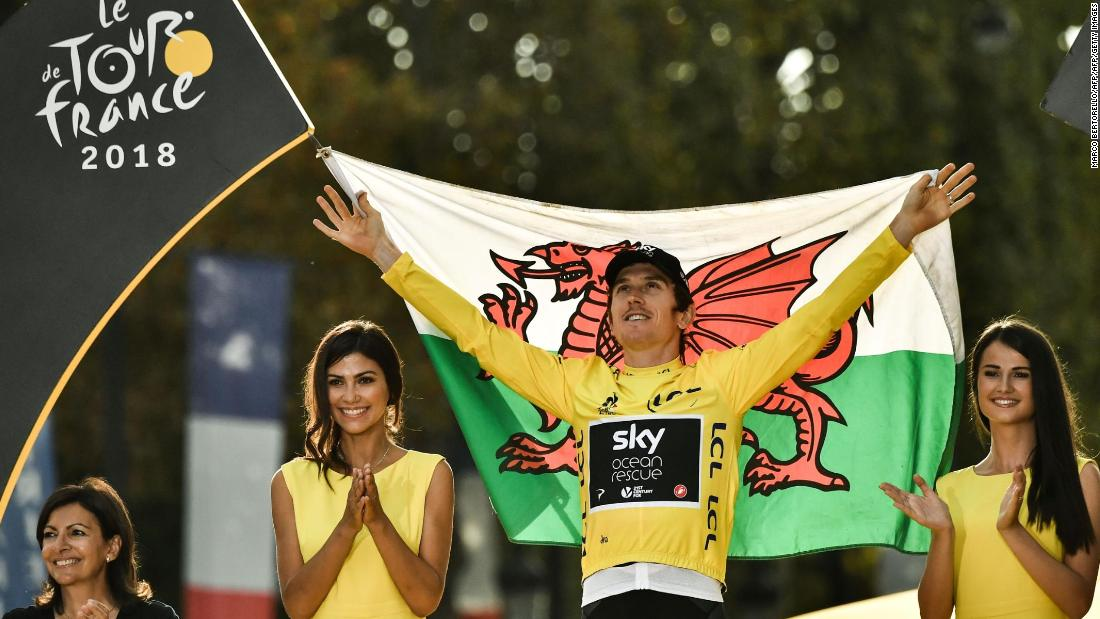Tour de France 2018 winner Geraint Thomas  holds the Welsh flag as he celebrates on the podium in Paris.