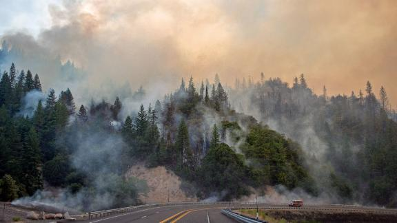 A fire truck drives along Highway 299 as the Carr fire continues to burn near Whiskeytown on July 28.