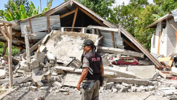 An Indonesian village security officer examines the remains of houses, after a 6.4 magnitude earthquake struck, in Lombok on July 29, 2018. - A powerful earthquake on the Indonesian tourist island of Lombok killed at least 10 people, injured dozens and damaged hundreds of homes on July 29, officials said. (Photo by Aulia AHMAD / AFP)        (Photo credit should read AULIA AHMAD/AFP/Getty Images)