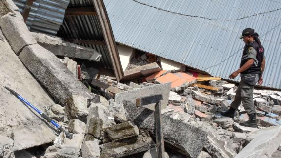 An Indonesian village security officer examining the debris of houses, after a 6.4 magnitude earthquake struck, in Lombok on July 29.