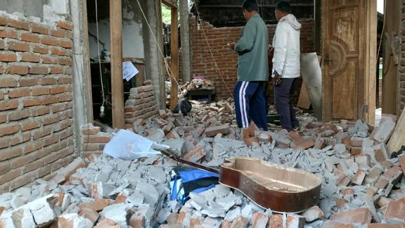 Villagers walk through a house that was damaged after a 6.4 magnitude earthquake struck in Lombok on July 29.