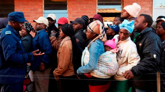 People queue to vote early Monday morning.