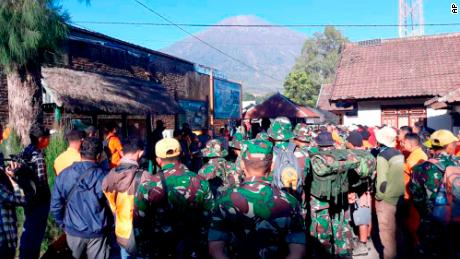 Indonesian soldiers and rescue workers gather to evacuate tourists from Mount Rinjani in the background, at Sembalun in East Lombok, Indonesia, Monday, July 30.