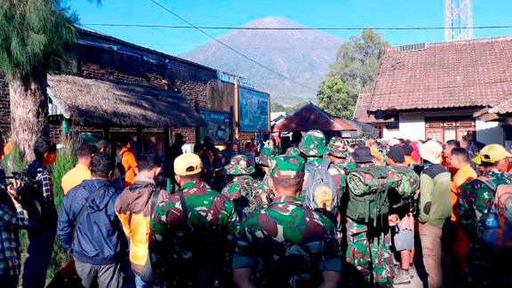 Indonesian soldiers and rescue teams gather to prepare for evacuating tourists from Mount Rinjani, seen in the background, at Sembalun in East Lombok on Monday.