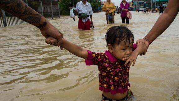 Residents hold onto a child as they walk through floodwaters in the Bago region, some 68 km away from Yangon, on July 29, 2018. -