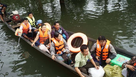 Burmese citizens wearing bright orange vests board rescue boats.