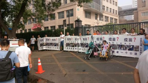 Small group of protestors hold a rare public demonstration over the vaccine scandal in front of China's National Health Commission in Beijing on Monday July 30.