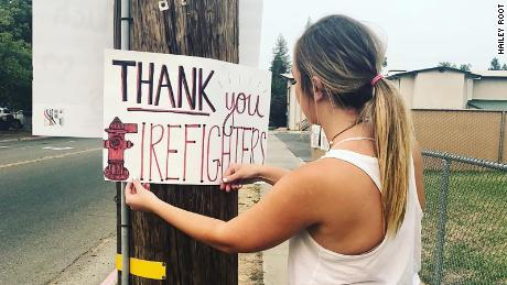 Root putting up a sign thanking the firefighters battling the Carr Fire.