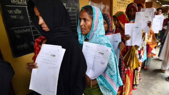 Residents hold their documents as they stand in a queue to check their names on the final list of National Register of Citizens (NRC) at a NRC Sewa Kendra (NSK) in Burgoan village in Morigoan district on July 30, 2018. - India on July 30 stripped four million people of citizenship in the northeastern state of Assam, under a draft list that has sparked fears of deportation of largely Bengali-speaking Muslims. Critics say it is the latest move by right-wing Prime Minister Narendra Modi to advance the rights of India