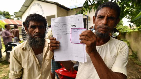 A resident holds documents on his way to check his name on the final list of National Register of Citizens (NRC) in Kuranibori village, in Assam