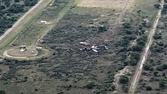 Rescue crews flock to the remains of the airplane just beyond the runway.