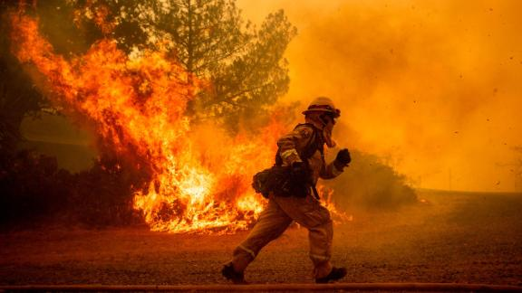 A firefighter runs while trying to save a home as a wildfire tears through Lakeport, Calif., Tuesday, July 31, 2018. The residence eventually burned. Firefighters pressed their battle against a pair of fires across Mendocino and Lake counties. In all, roughly 19,000 people have been warned to flee and 10,000 homes remain under threat. Noah Berger/AP