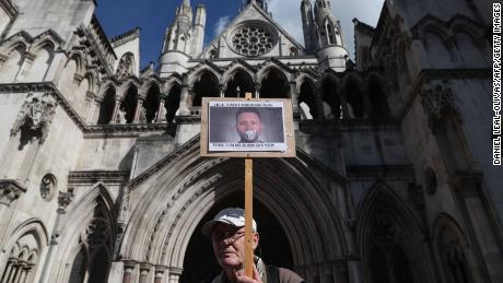 A supporter of Tommy Robinson is seen holding a placard outside the Royal Courts of Justice in London on Wednesday.