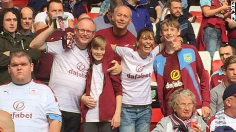 Gail and Simon Astin watching Burnley at Anfield with their two sons last season.
