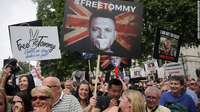 Protesters hold up placards at a gathering by supporters of far-right spokesman Tommy Robinson in central London on June 9, 2018.