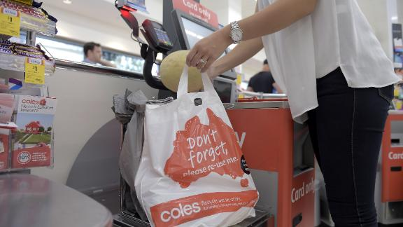 A customer places grocery items into a plastic bag at a self checkout counter in a Coles supermarket in Melbourne.