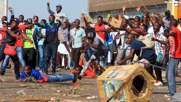 Opposition party supporters react after police fire tear gas in Harare, Zimbabwe.