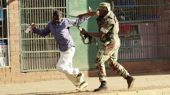 A Zimbabwean soldier beats a man in a street of Harare on Wednesday, August 1.