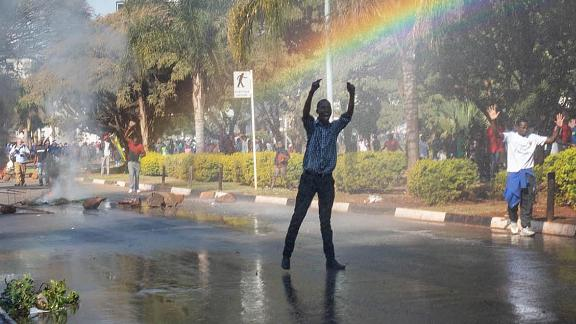 A protester gestures toward police water cannons outside of the gates of the ZImbabwe Electoral Commission (ZEC).