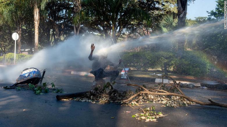 A protester is hit in the face with a water cannon Wednesday outside the gates of the Zimbabwe Electoral Commission in Harare.