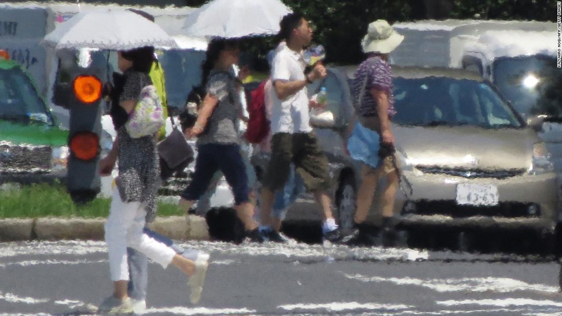 The effects of heat haze are seen in this photograph as pedestrians cross a street in Tokyo on Thursday, August 2.