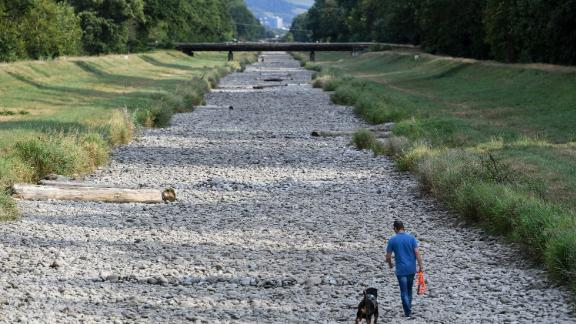 A man walks his dog in the dry riverbed of the Dreisam in Freiburg, Germany, on August 1.