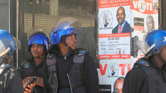 A Zimbabwean Riot policeman looks at the campaign poster of main opposition leader, Nelson Chamisa outside the party headquarters in Harare, Zimbabwe, Thursday, Aug, 2, 2018. Zimbabwe's acting President said Thursday that his government had been in touch with the main opposition leader in an attempt to ease tensions after election related violence in the capital. (AP Photo/Tsvangirayi Mukwazhi)