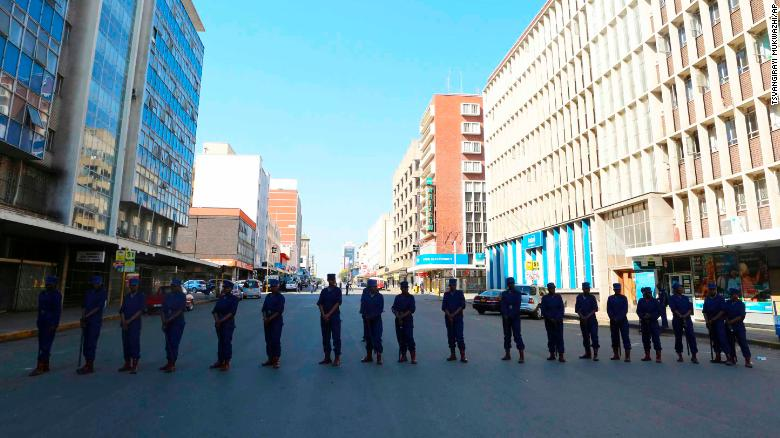 Zimbabwe police officers block the road leading to the opposition offices in the capital Harare on Thursday.