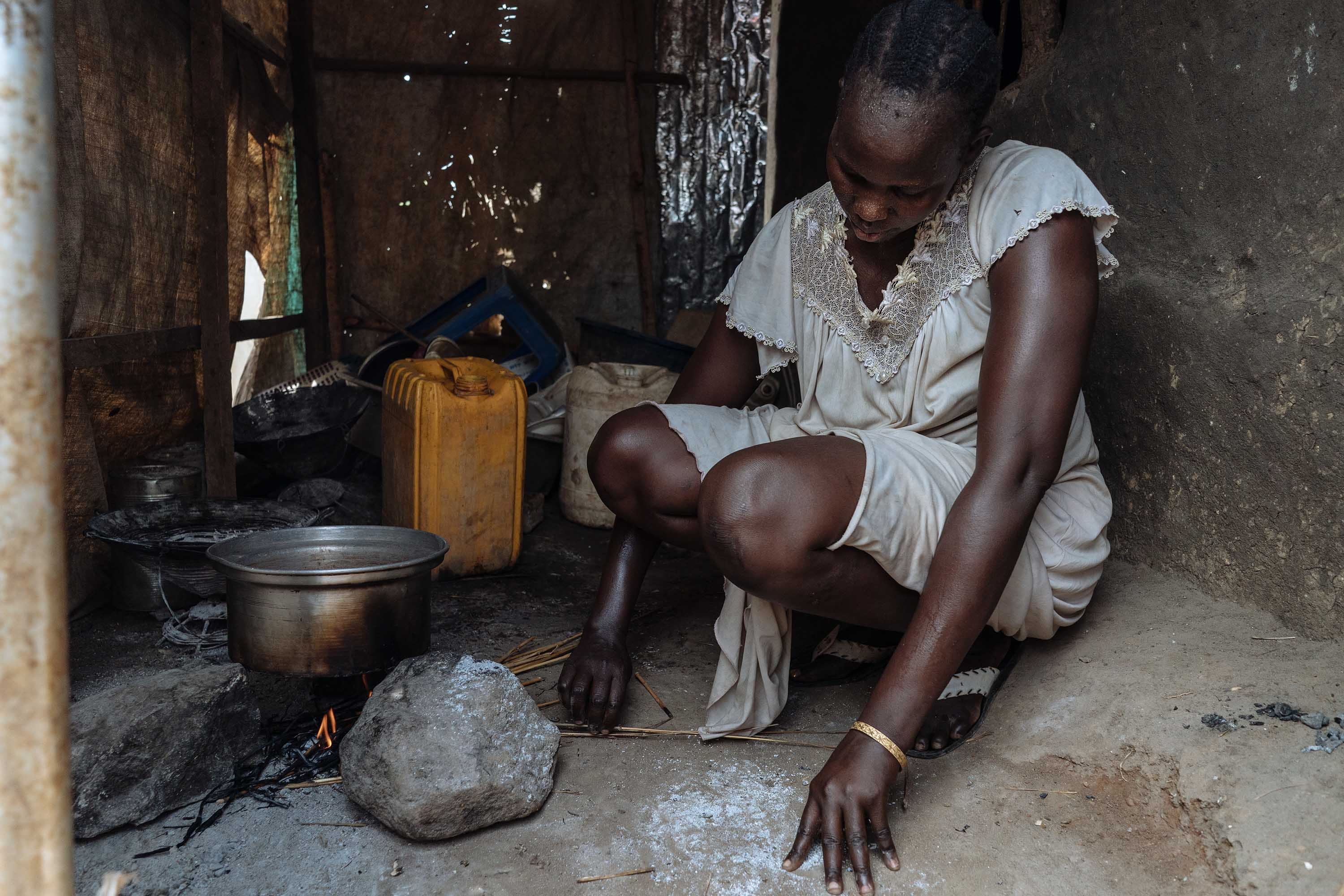 Angeline, a South Sudanese woman, photographed making a fire in her kitchen.
