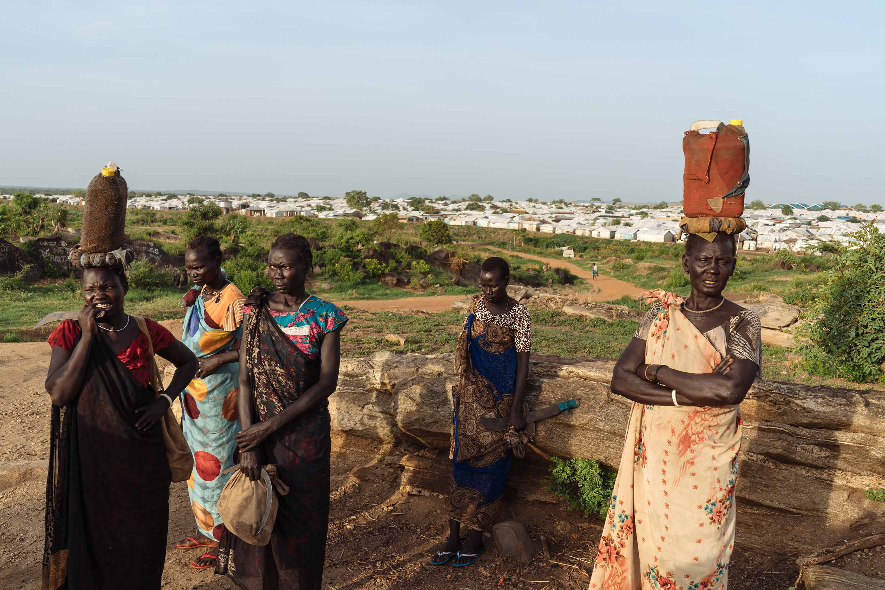 South Sudanese women wait for others to join on the way to the forest to get firewood.