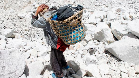 Local porters working on Everest lug the barrels down from base camp to Gorak Shep, a frozen lakebed 17,000 feet above sea level.