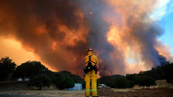 A tower of smoke pours from Cow Mountain as a firefighter keeps a watch on surrounding vegetation.