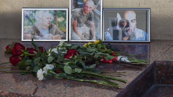 A picture taken on August 1, 2018 shows flowers left in front of the photographs of Russian journalists (L-R) Alexander Rastorguyev, Kirill Radchenko and Orkhan Dzhemal, who were recently killed in the Central African Republic, outside the Central House of Journalists. (Photo by Vasily MAXIMOV / AFP)        (Photo credit should read VASILY MAXIMOV/AFP/Getty Images)