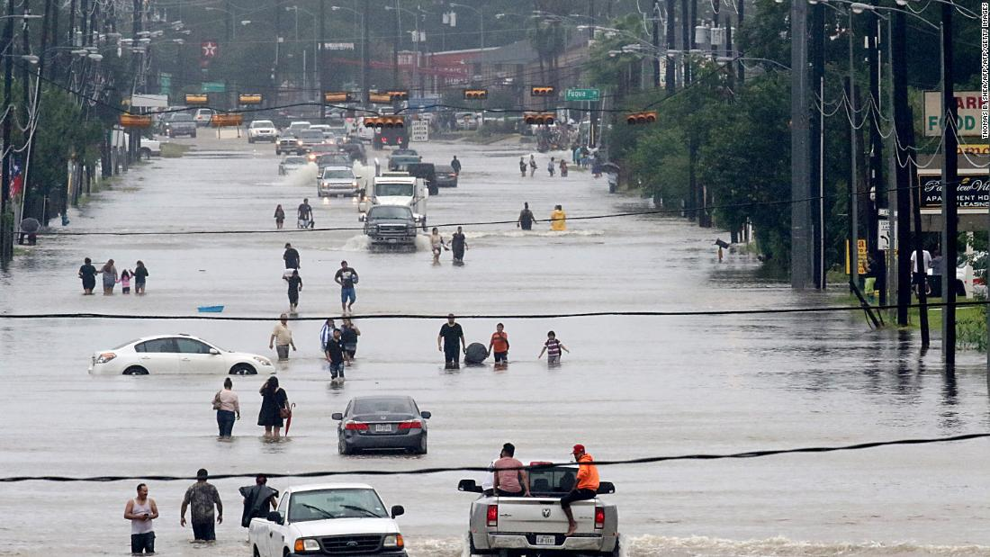 People walk through flooded roads in Houston, Texas, on August 27, 2017 as Hurricane Harvey hit the city.