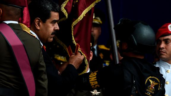 """Venezuelan President Nicolas Maduro (L) attends a ceremony to celebrate the 81st anniversary of the National Guard in Caracas on August 4, 2018. - Maduro was unharmed after an exploding drone """"attack"""", the minister of communication Jorge Rodriguez said following the incident, which saw uniformed military members break ranks and scatter after a loud bang interrupted the leader's remarks and caused him to look to the sky, according to images broadcast on state television. (Photo by Juan BARRETO / AFP)        (Photo credit should read JUAN BARRETO/AFP/Getty Images)"""