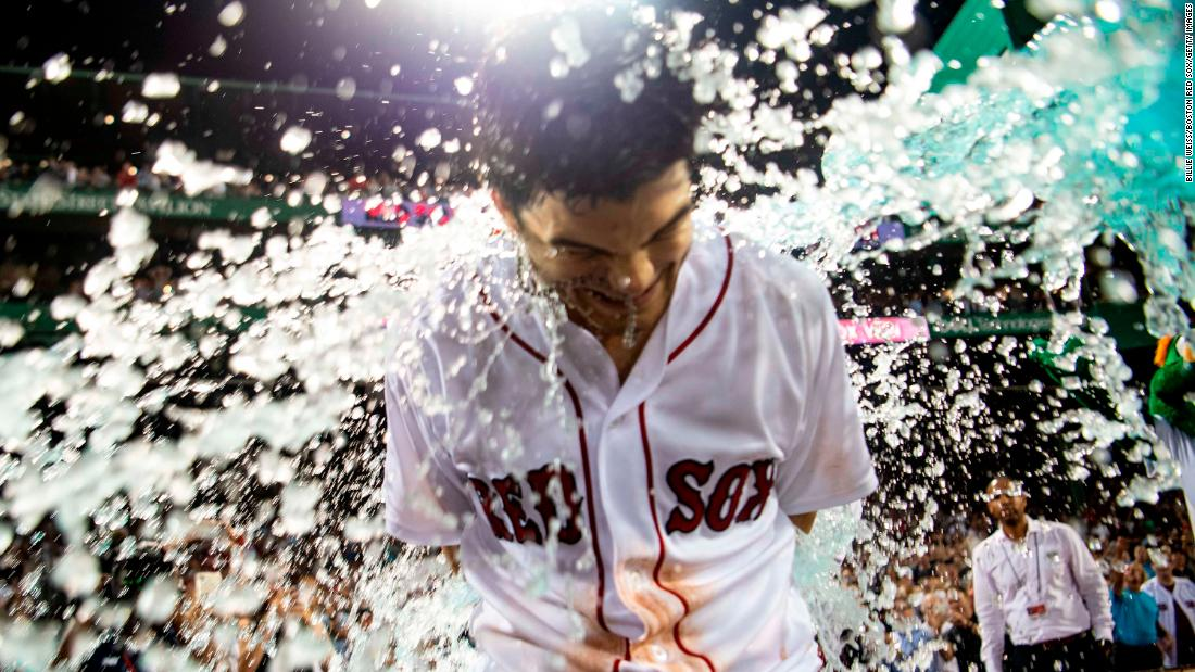 Andrew Benintendi of the Boston Red Sox is doused in Gatorade after hitting the game winning walk-off single during the tenth inning against the New York Yankees on Sunday, August 5, at Fenway Park in Boston, Massachusetts.