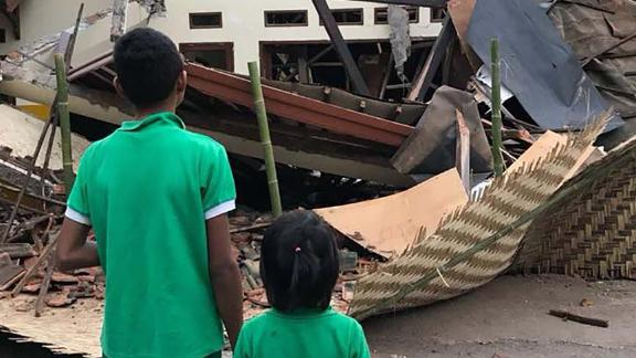 Children from the Peduli Anak Foundation stand outside the destroyed home.